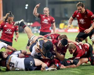 Brendon O'Connor of the Crusaders is driven over under a pile of fellow forwards to score a try...