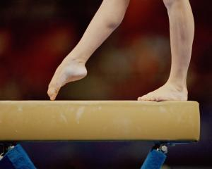 Female gymnast competes on balance beam. Photo: Getty Images
