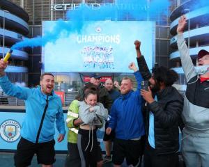 Manchester City fans celebrate winning the English Premier League outside the Etihad Stadium....