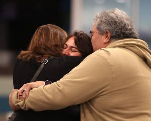 Jonathan and Carol Penfold hug their daughter Alice at Christchurch Airport. Photo: George Heard