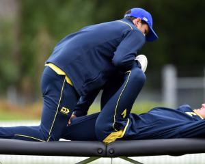 Physiotherapist Brett Harrop works on injured all-rounder Nathan Smith during an Otago Volts team...