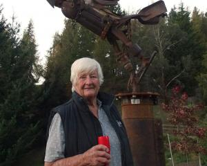 Jill Blennerhassett stands in front of her latest commissioned metal sculpture, mounted in the...