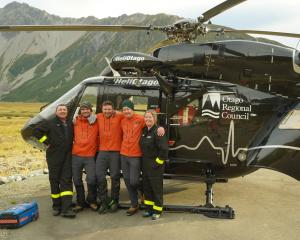 Celebrating the successful mission at the Mount Cook rescue base helipad are (from left) former...