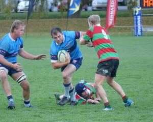 Wakatipu openside flanker Dave Fraser gives Matakanui Combined's Luke Hume the flick, with team...