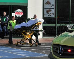 A patient is wheeled to an ambulance after the stabbing in Countdown Dunedin Central today. Photo...