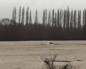 The occupants of this car managed to get out before the vehicle floated down Taylors Stream in...