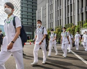 Medical workers arrive at a newly opened mass vaccination site in Tokyo yesterday as Japan's...