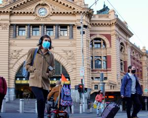 Pedestrians outside Melbourne's Flinders Street Station on the first day of eased Covid...