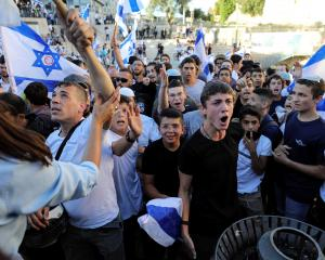 Israelis hold flags and shout by Damascus Gate, just outside Jerusalem's Old City on Tuesday....