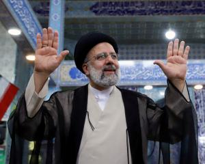 Ebrahim Raisi gestures after casting his vote during presidential elections at a polling station...
