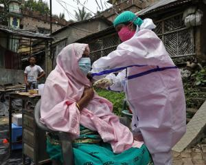 A villager receives a Covid-19 vaccination at Uttar Batora Island in Howrah district in West...