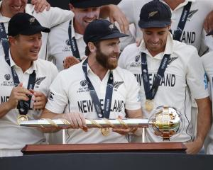 Kane Williamson (centre) and members of the New Zealand team celebrate with the trophy after...