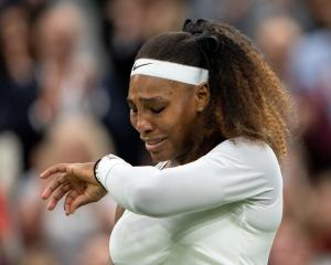 Serena Williams reacts after sustaining an injury before retiring from her first round match...