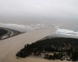 Sediment-laden floodwater pours out of the mouth of the Waimakariri River at Pines Beach, north...