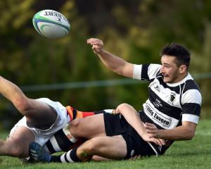 Southern halfback Wilson Driver seeks to pass the ball up in the tackle of Zingari-Richmond first...