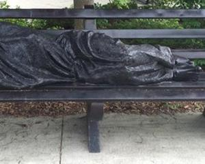 The Homeless Jesus sculpture lies on a bench at the campus of King's University College at...