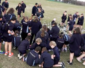Pupils from St Patrick's School pick up the golf balls. Photo: Geoff Sloan