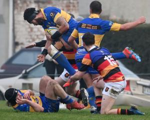 Taieri lock Don Lolo carries the ball in traffic as teammates Mark Rooney (on ground) and Brayden...