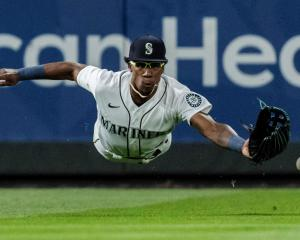 Seattle Mariners leftfielder Shed Long jun dives for a ball during his team's Major League game...
