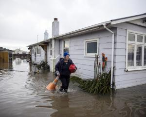 A Westport resident leaves her home after the weekend's flooding. PHOTO: THE NEW ZEALAND HERALD
