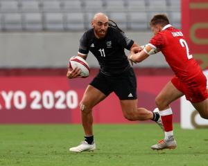 New Zealand's Joe Webber fends off a tackle from Canada's Theo Sauder on  Tuesday. Photo: Reuters