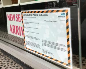 One of the placards displayed in a shop window along East St. Photo: Ashburton Courier