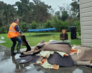 Peter Bailey, of Westport, adds to a pile of sodden carpet outside his house yesterday. PHOTO:...