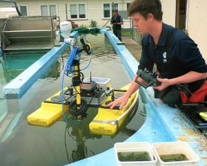 Niwa freshwater ecologist Dr Daniel Clements trials a submerged invasive weed detector that uses...