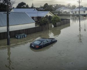 A partly-submerged car outside flooded Westport houses. Photo: Supplied/NZ Defence Force