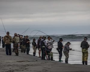 Entrants in the Rangers Fishing Competition line the banks of the river mouth. Photo: Richard...