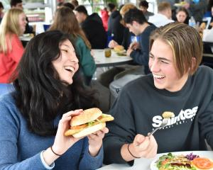 Enjoying a meat-free schnitzel at Aquinas College yesterday are sub-warden Sara Aruquipa and...