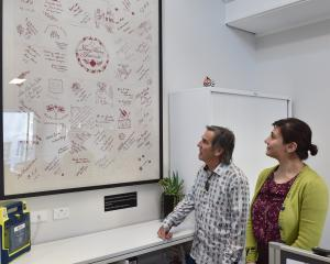 Red Cross staff Steve King and Mona Tavakoli with a   World War 1-era quilt,  at their office in...