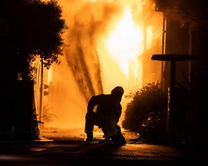A firefighter works to douse flames at a large fire in Westport early today. Photo: NZ Herald