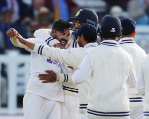 India's Mohammed Siraj celebrates with teammates after taking the wicket of England's Jos Buttler...