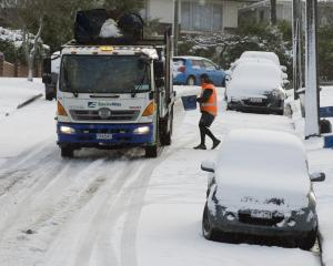 Bins continue to be emptied despite the snow at Turner St yesterday morning. PHOTO: GERARD O'BRIEN