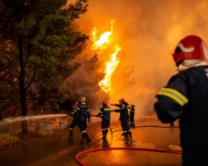 Crews battle a forest fire approaching a gas station in a wooded area north of Athens. Photo: Getty