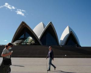 People exercise at a distance from reach other beside the forecourt of the Sydney Opera House...