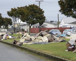 Carpets and waste line the streets of Westport after floods last month. PHOTO: GREYMOUTH STAR