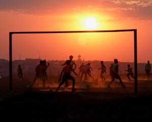 Locals play football on a dusty pitch in Soweto, South Africa. REUTERS