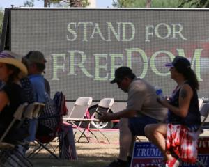 Supporters of former US President Donald Trump sit outside the Senate while listening to the...