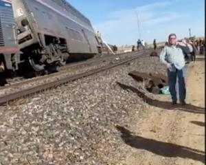People wait at the side of train tracks at the scene of an Amtrak train derailment near Havre,...