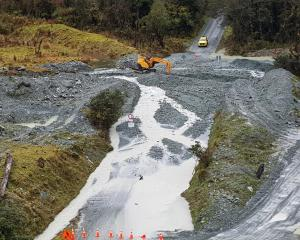 Workers clear a river crossing on the Hollyford Rd, in Fiordland National Park, which will take '...