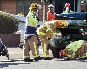 Firemen inspect the damage to a car that hit a power pole at the intersection of Prince Albert Rd...