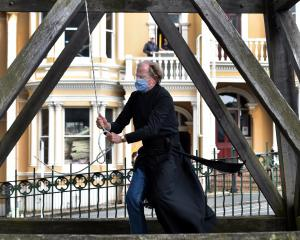 Minister Bruce Aitken rings the bell outside St Paul's Cathedral, in Dunedin, at 1pm yesterday,...