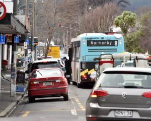 A bus parks in the street to pick up passengers at a bus stop on North Rd near the Dunedin...