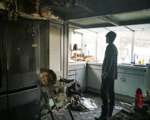 Tanner (16) surveys the damage to his family's home after it was destroyed by fire last week....