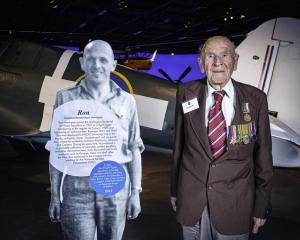 Ron Hermanns standing with a cut-out figure of his younger self at the Air Force Museum of New...