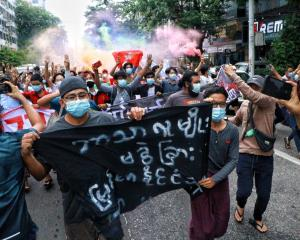 Protesters take part in a demonstration in Yangon on July 7 against the military coup and to mark...