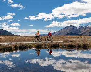 Cyclists are reflected in a pond near Kingston on the Around the Mountains Cycle Trail. PHOTO:...