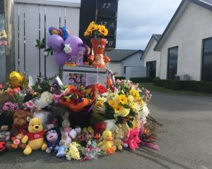 An ever-increasing collection of flowers and toys have been laid on the driveway of the Queen St...